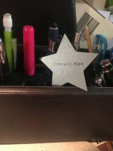 "a photo of a desk organizer and a small star that says ""conviction"" on it."
