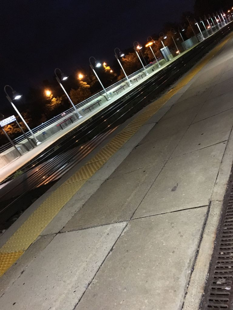 an empty train station platform in pre-dawn darkness